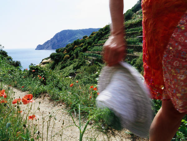 Woman on Cinque Terre pathway near coast.