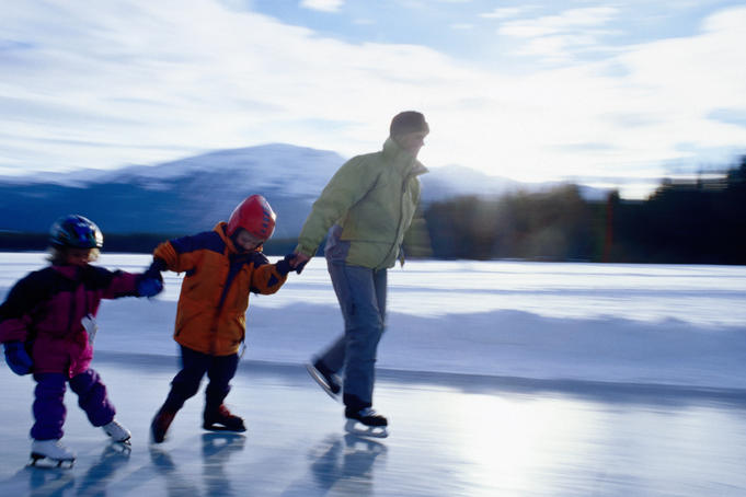 Family skating on frozen lake.