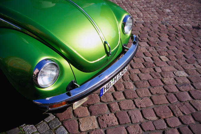 Detail of green Volkswagen parked on cobblestone street.
