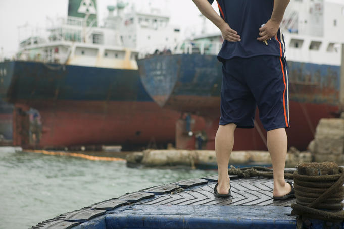 Man standing on deck of small cargo vessel in Busan Harbor.