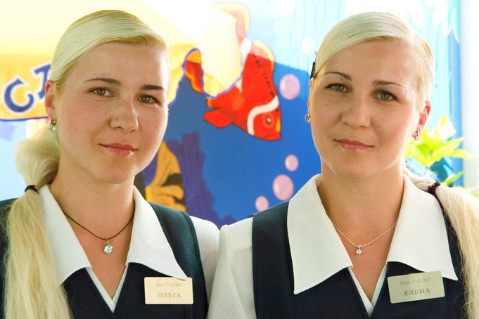 Twin female waiters with long blond hair at seaside bar.