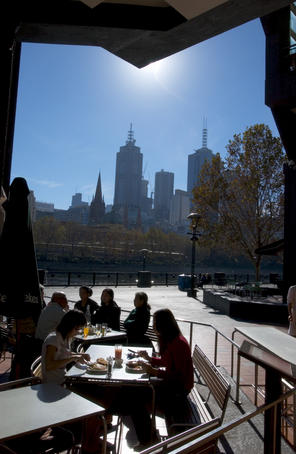 People dining alfresco at Southbank with city high-rises beyond.