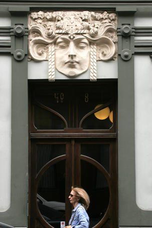 Woman walking past door of Art Nouveau building in old town Riga.