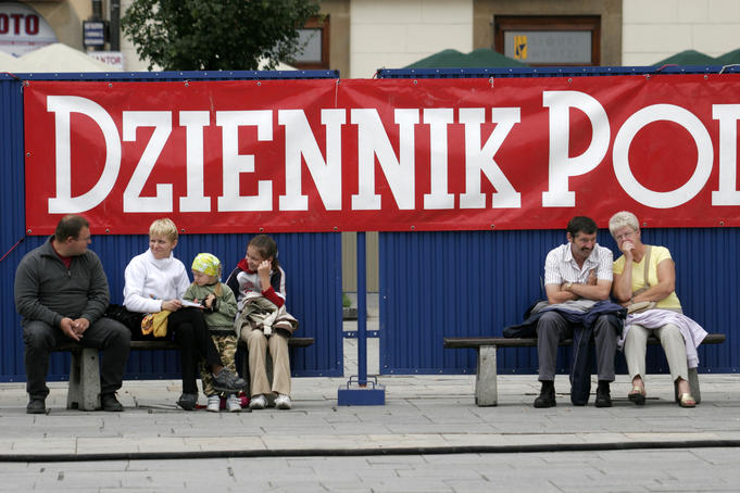 Locals and newspaper banner on Rynek Glowny.