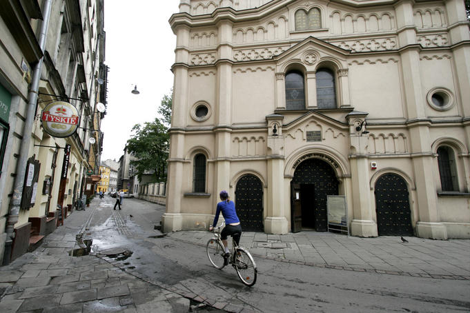 Person riding bike through old Jewish quarter, with Synagoga Tempel in background.