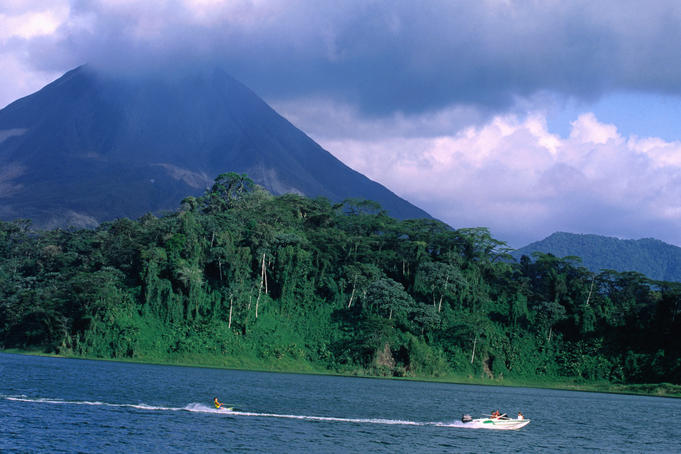 Tropical rain forest, lake with Volcano in background.