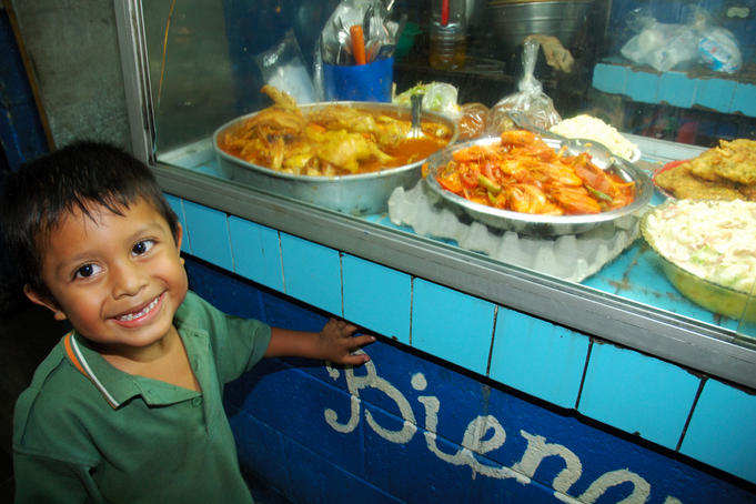 Young boy in front of food for sale in background at Mercado San Miguel.