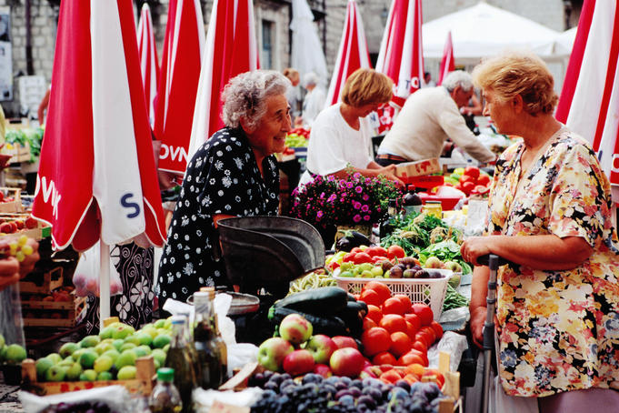 Trader and customer at morning market on Gunduliceva Poljana in old town.
