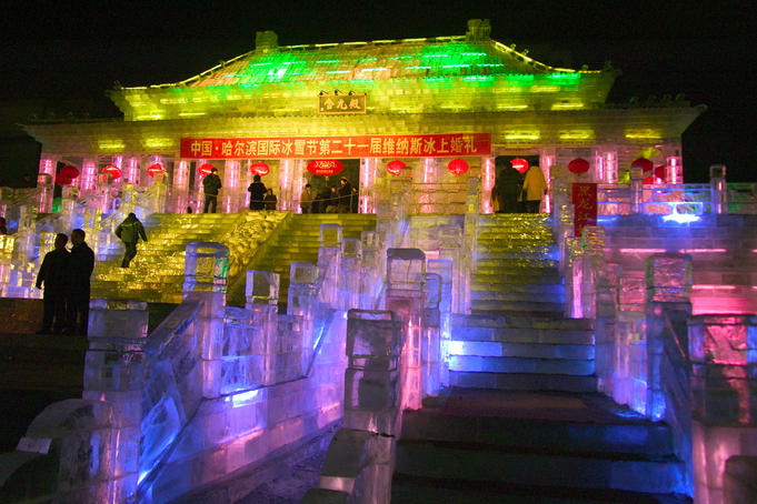 Illuminated ice sculpture of traditional architecture at Ice Festival.