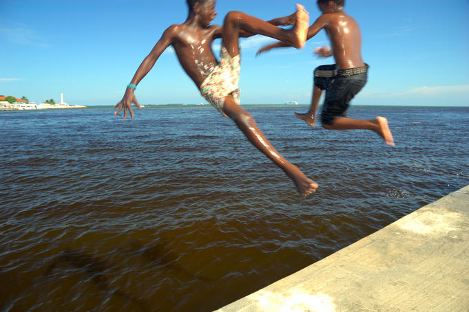 Kids leaping off marina into Haulover Creek, Belize Bay.