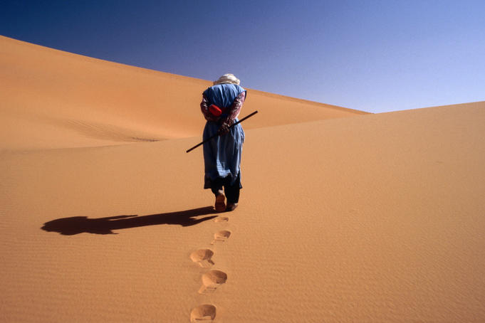 Local man walking in the Sahara.