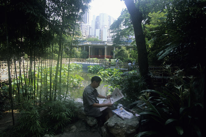 Man reading newspaper in Lou Lim Ieoc Garden.