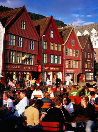 People sitting at outdoor tables at Bryggen Wharf.