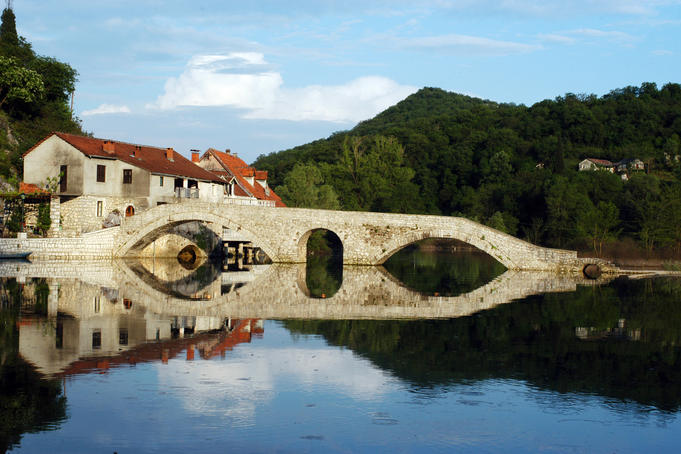 Four-arched bridge of Rijeka Crnojevica reflected in Lake Skadar.
