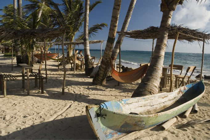Traditional canoe, palm trees and thatched roof shacks on beach at Miss Elsa's, with couple in background, Little Corn Island.