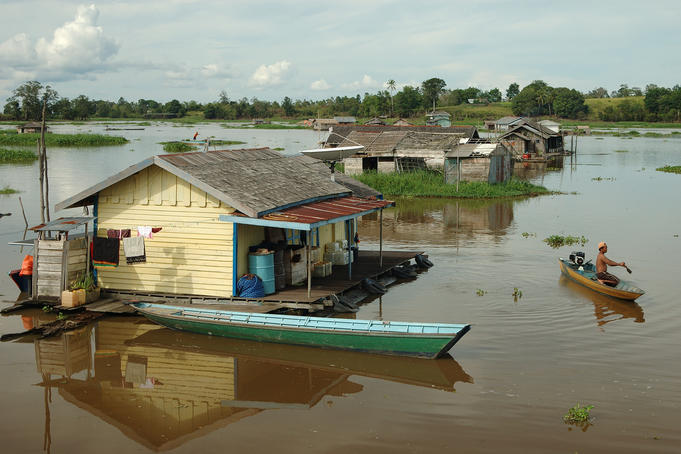 Man on motorised boat near floating houses.
