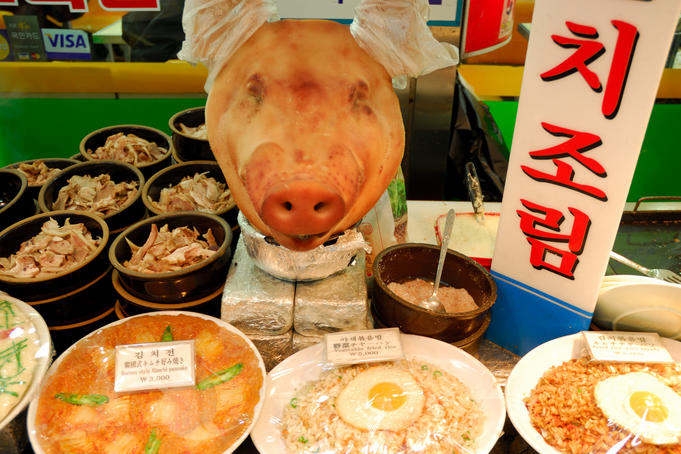 Pig's head amongst dishes for sale at Namdaemun Market.