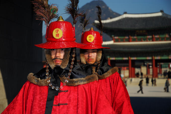 Gyeongbokgung palace guards with palace, mountains in background, Gwanghwamun.