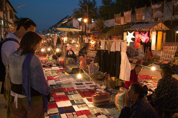 Customers at stall at night market.