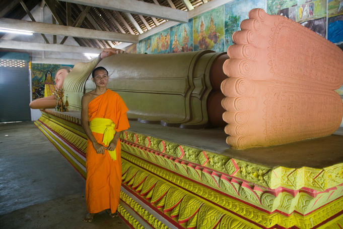 Yyoung monk in front of reclining Buddha, Wat Rathana Ransi.