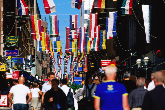 Drottninggatan, shoppers below flags.