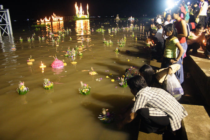 Thai families placing lighted krathong (votive candles & flowers) on Chao Phraya River during Loi Krathong lantern festival at Bangsai Royal Folk Arts and Crafts Centre.