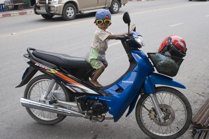 Young motorcyclist with goggles on stationary motorcycle.