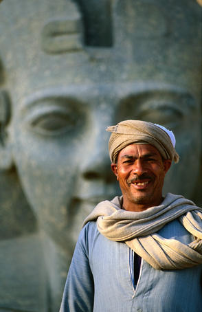 Man in front of Ramses II statue, Luxor Temple, East Bank of Nile River valley.