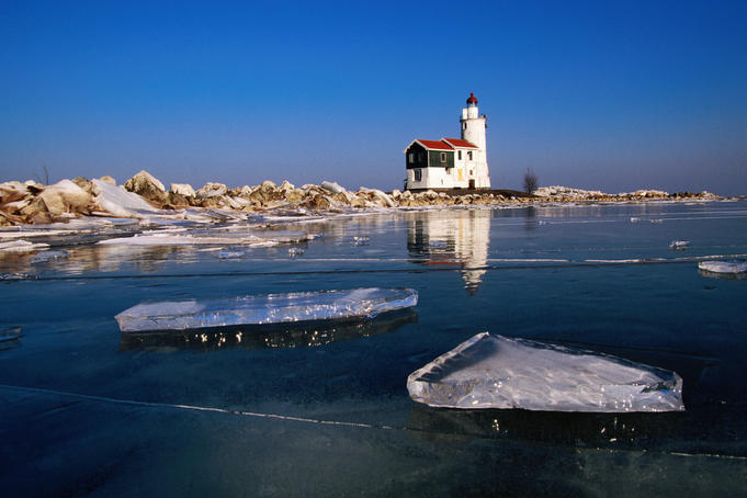 Lighthouse on frozen Ijsselmeer lake.