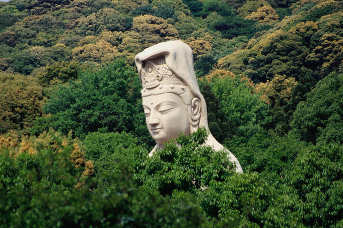 Statue of Kannon peeking through the trees around the Ryozen Kannon Temple, dedicated to the unknown soldiers who died during World War II.