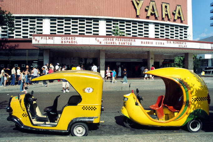 Coco taxis outside the cinema in Vedado.