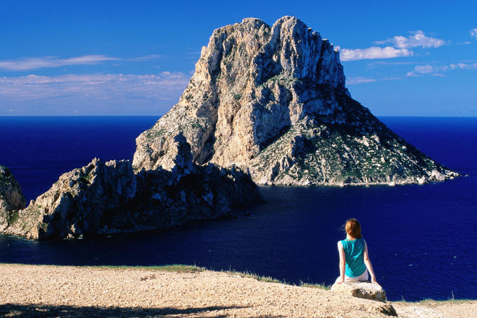 Near Sant Josep de Sa Talaia, girl on rock looking at offshore isle of Es Vedra.