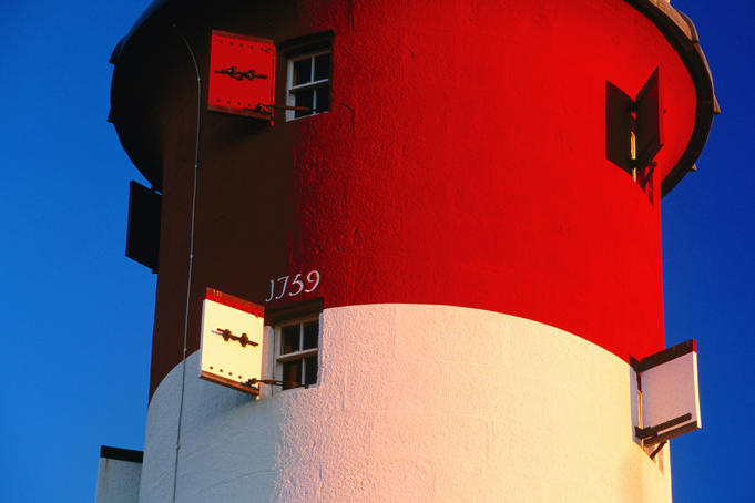 Detail of bright red and white Smeaton's Tower (formerly Eddystone Lighthouse) in late afternoon light.