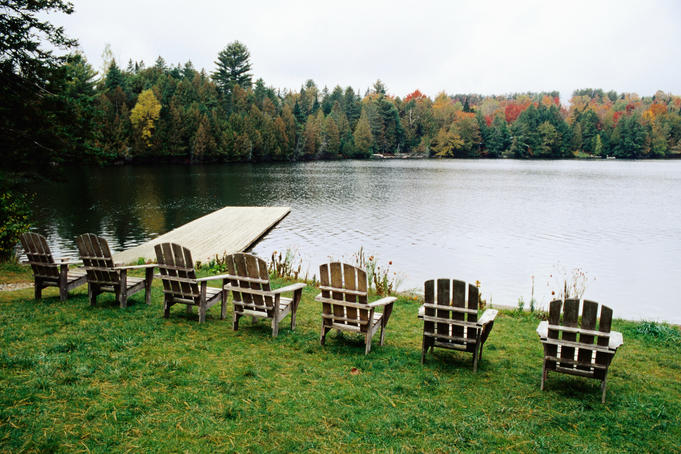 Adirondack chairs in row by lake, Northeast Kingdom.
