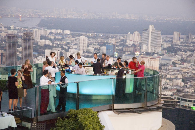 People around circular bar at Sirocco, with city buildings beyond.