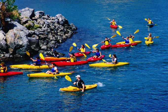 People kayaking in red and yellow kayaks.