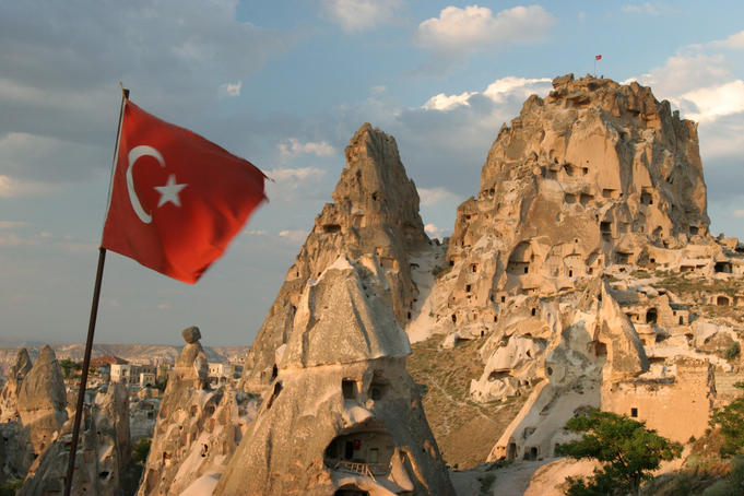 Turkish flag in front of Uchisar Castle.
