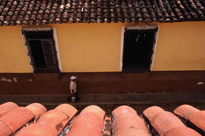 Overhead of roof tiles and man walking on cobbled street.