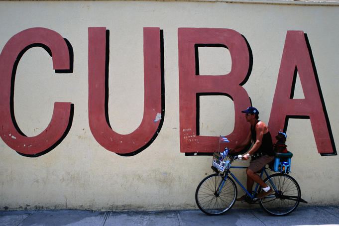 Man with dog riding past 'Cuba' mural.