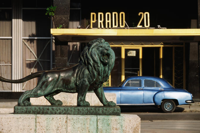Lion statue on Paseo del Prado (Paseo de Marti) with old car parked in background.
