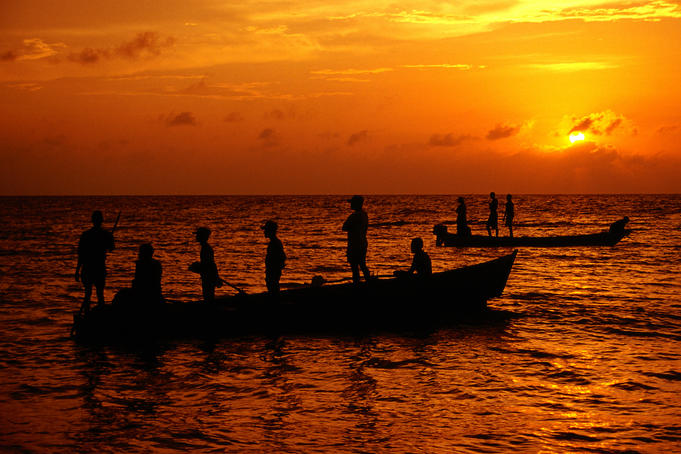 Fishermen waiting to pull nets in as sun sets over Caribbean Sea.