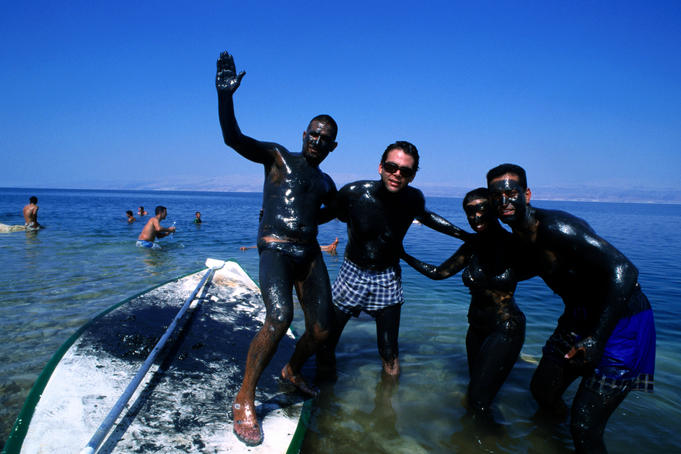 Tourists covered in mud at Dead Sea.