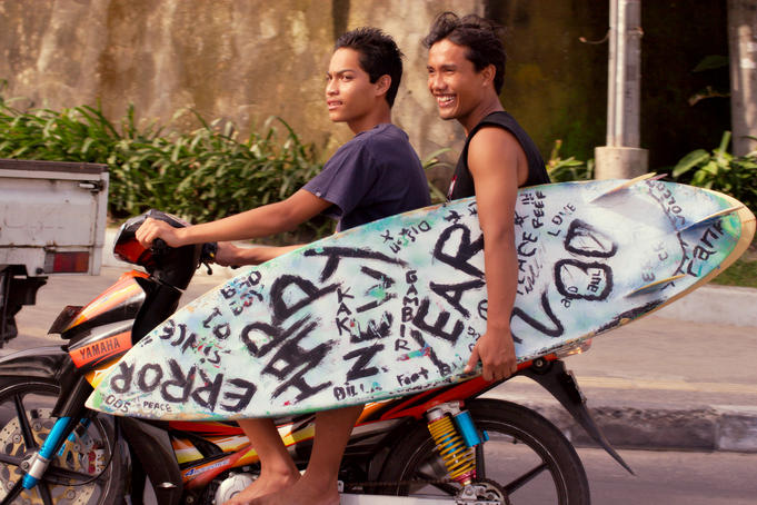 Two locals on motor bike with surfboard.