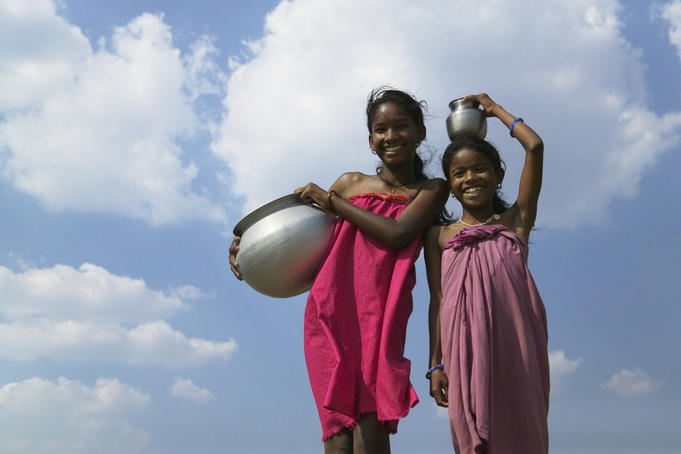 Low angle view of Indian girls carrying water jars.