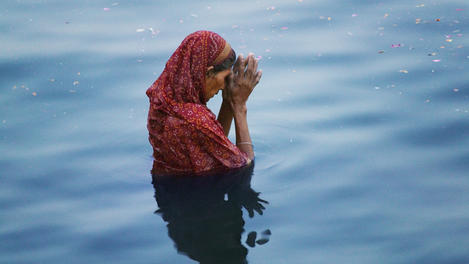 Woman praying in Ganges River.