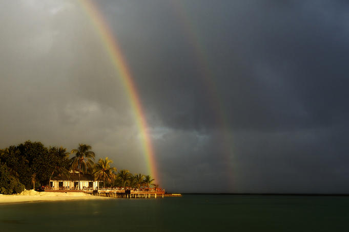 Rainbows over Full Moon resort bar during shower.