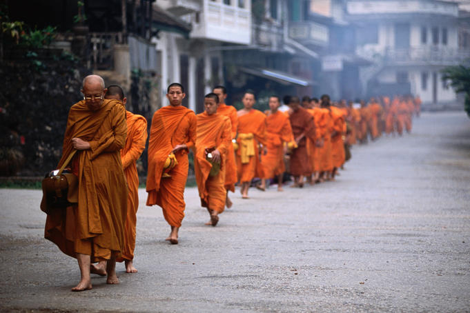 Monks on Tak Baat,or alms round, collecting food in morning.