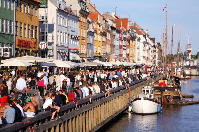 People at outdoor restaurants and young people along the canal, Nyhavn.