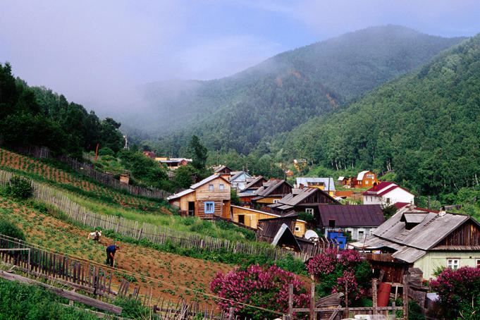 Houses in valley &amp; villagers working in Garden in Listvyanka village on Lake Baikal.