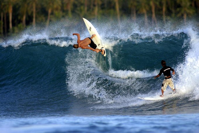 Brazilian surfer doing radical backhand re-entry while local surfer looks on.